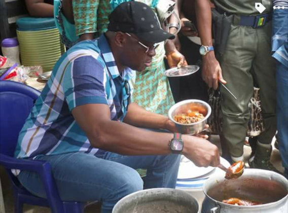 Photos: Fayose stops his convoy to dish beans from a bean sellers pot